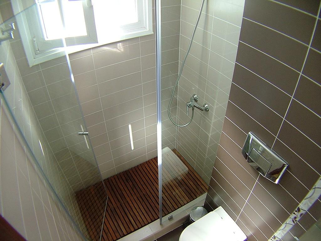 Reforma de baño con ducha de obra y tarima de madera con mampara sin perfiles